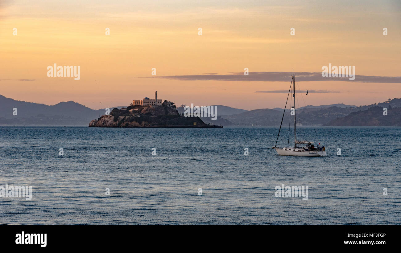 A sailboat goes by Alcatraz Island in San Francisco Bay at dusk - Stock Image