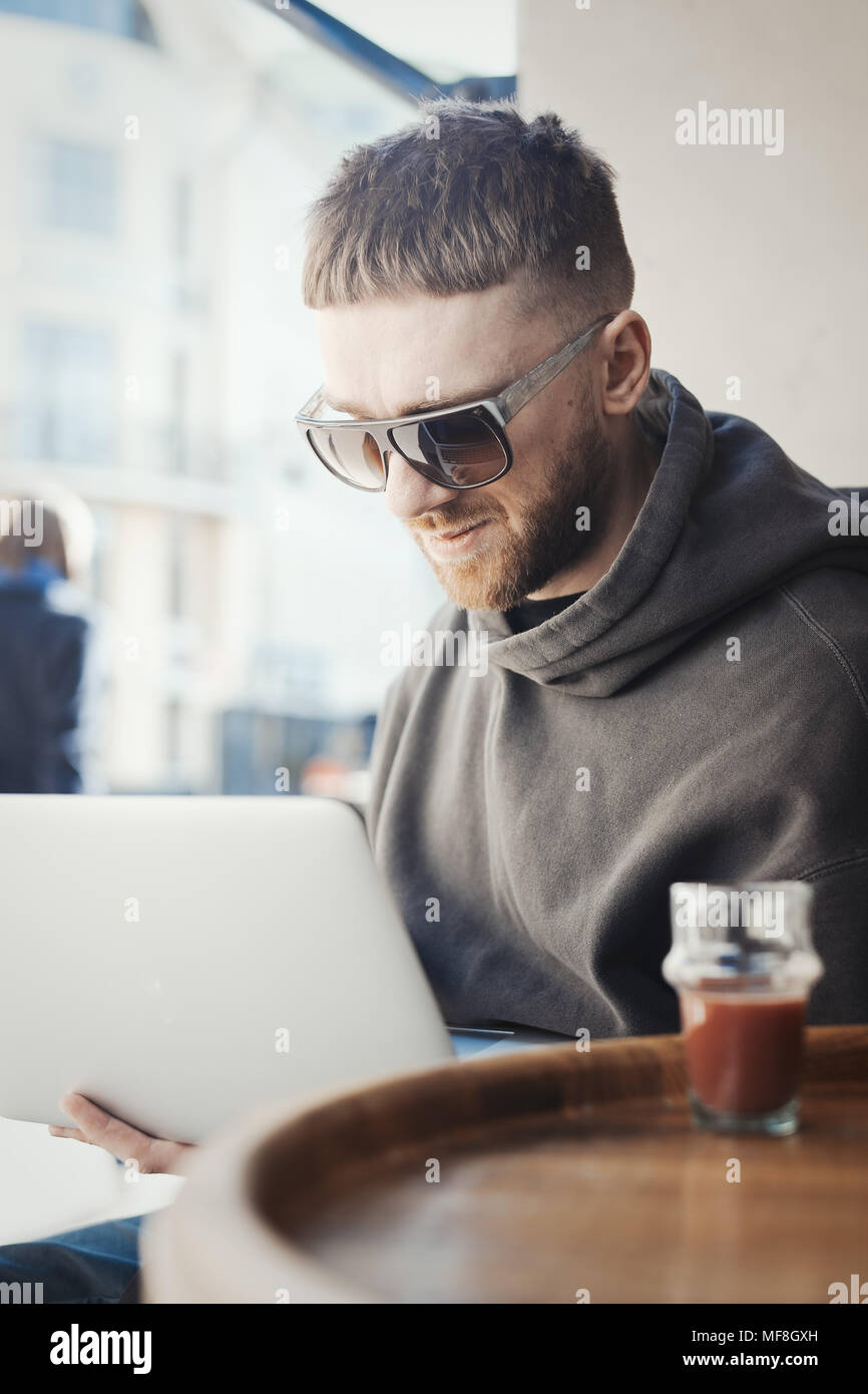 Pensive young man holding laptop on his knees and working on it in cafe. - Stock Image