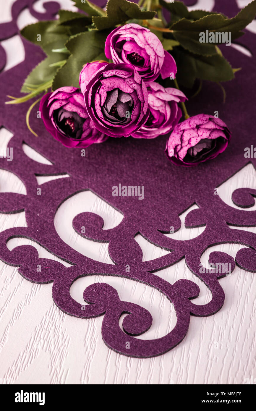 Dinner table with artificial flowers and colorful runners from felt cloth Stock Photo