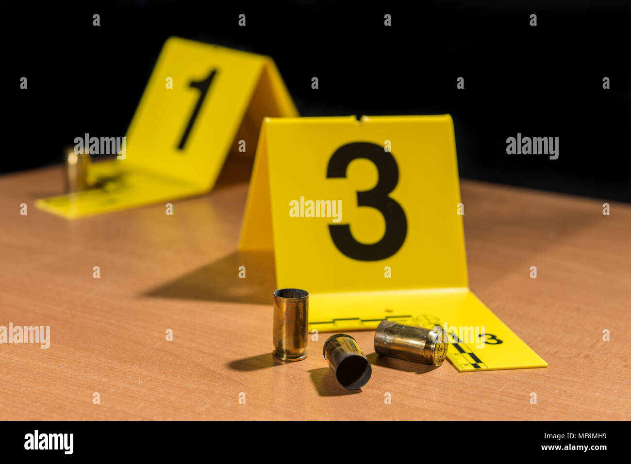 Expended bullet casings on a wood surface marked by crime scene evidence markers. - Stock Image