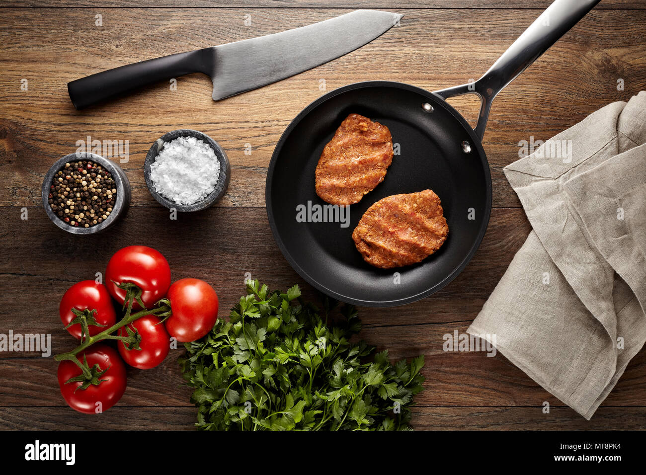 Raw meatballs in a black frying pan on a wooden table. Tomatoes, meat knife, napkin, parsley, black pepper and meat salt props are on the table. - Stock Image