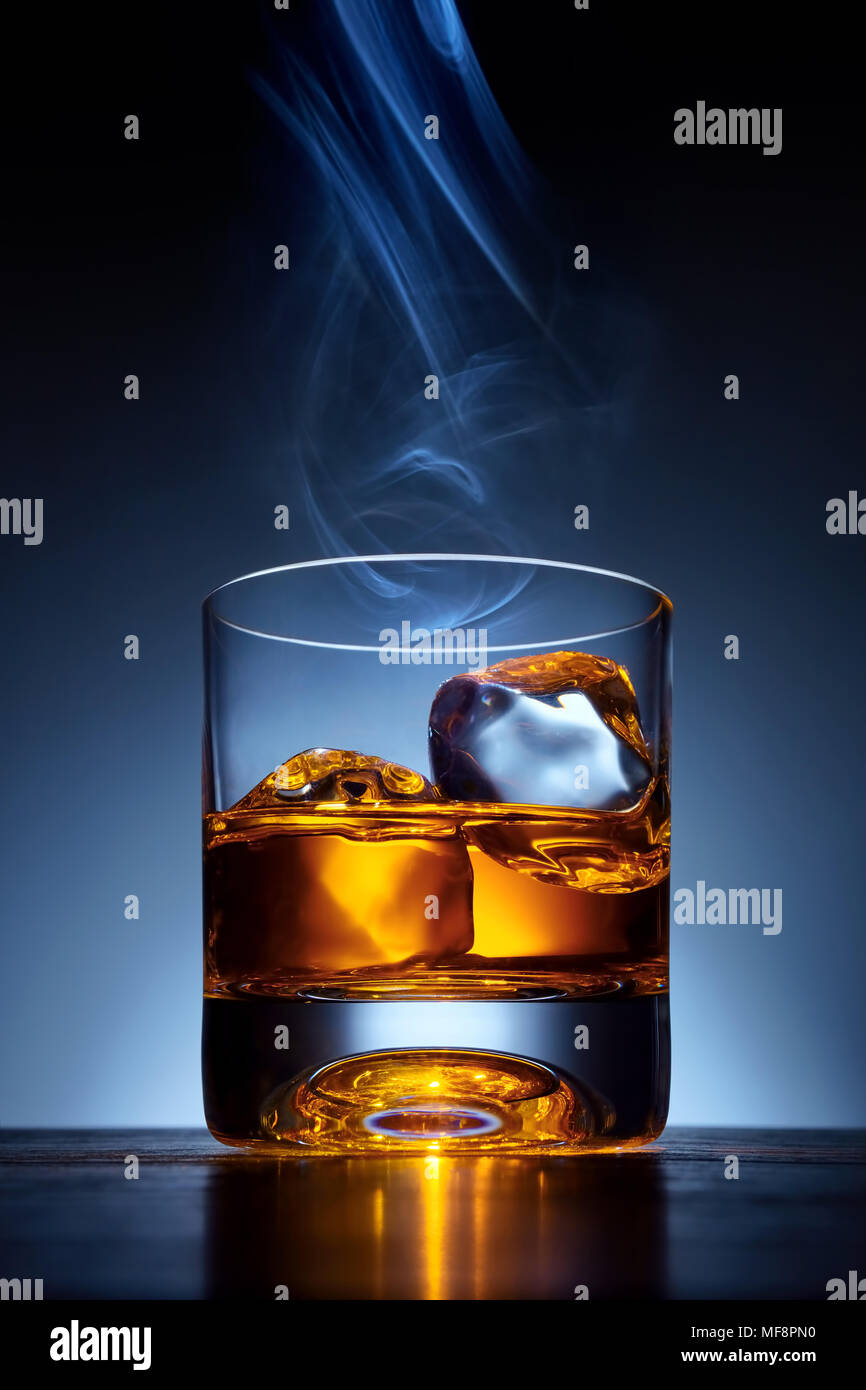 Single malt whiskey in a glass with ice on a wooden bar table with cigar smoke on the top of the glass - Stock Image