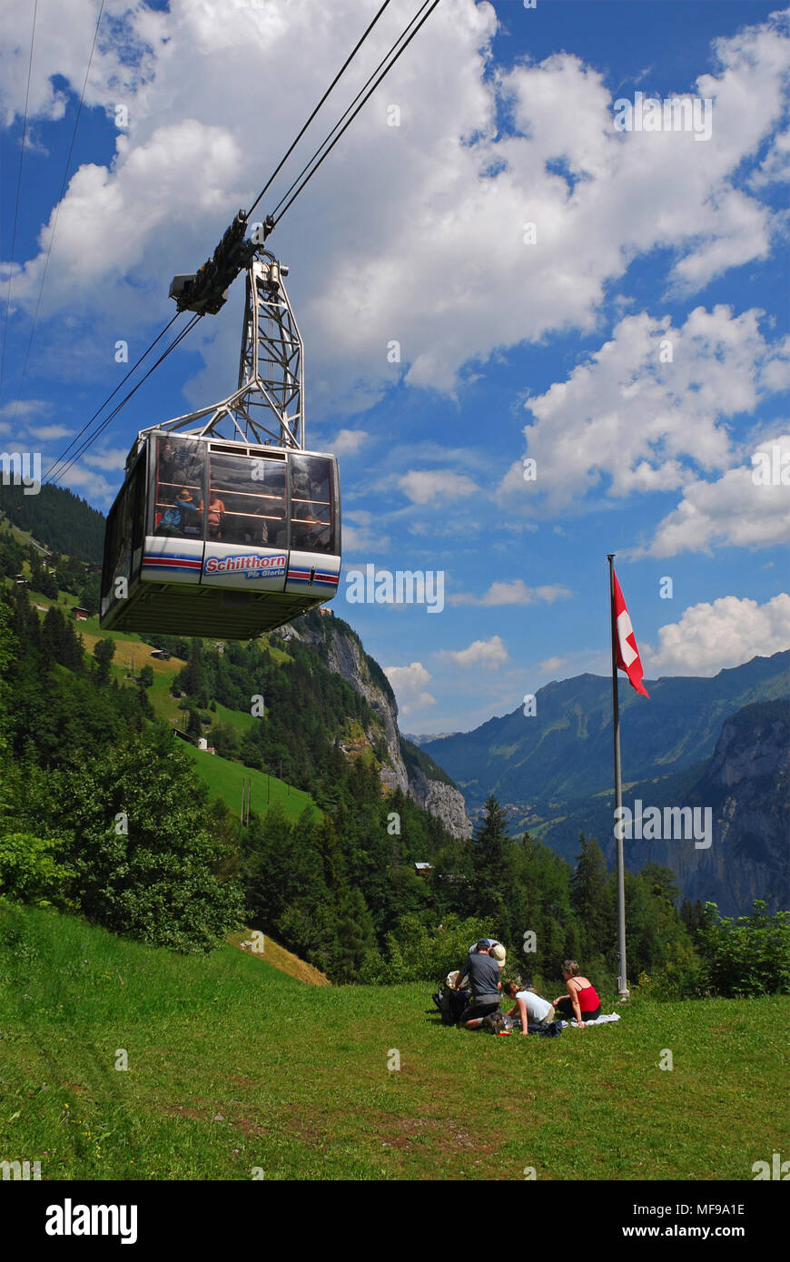 Schilthornbahn on the way from Gimmelwald to Schilthorn and people picnicking, Gimmelwald,Bernese Oberland , Switzerland Stock Photo