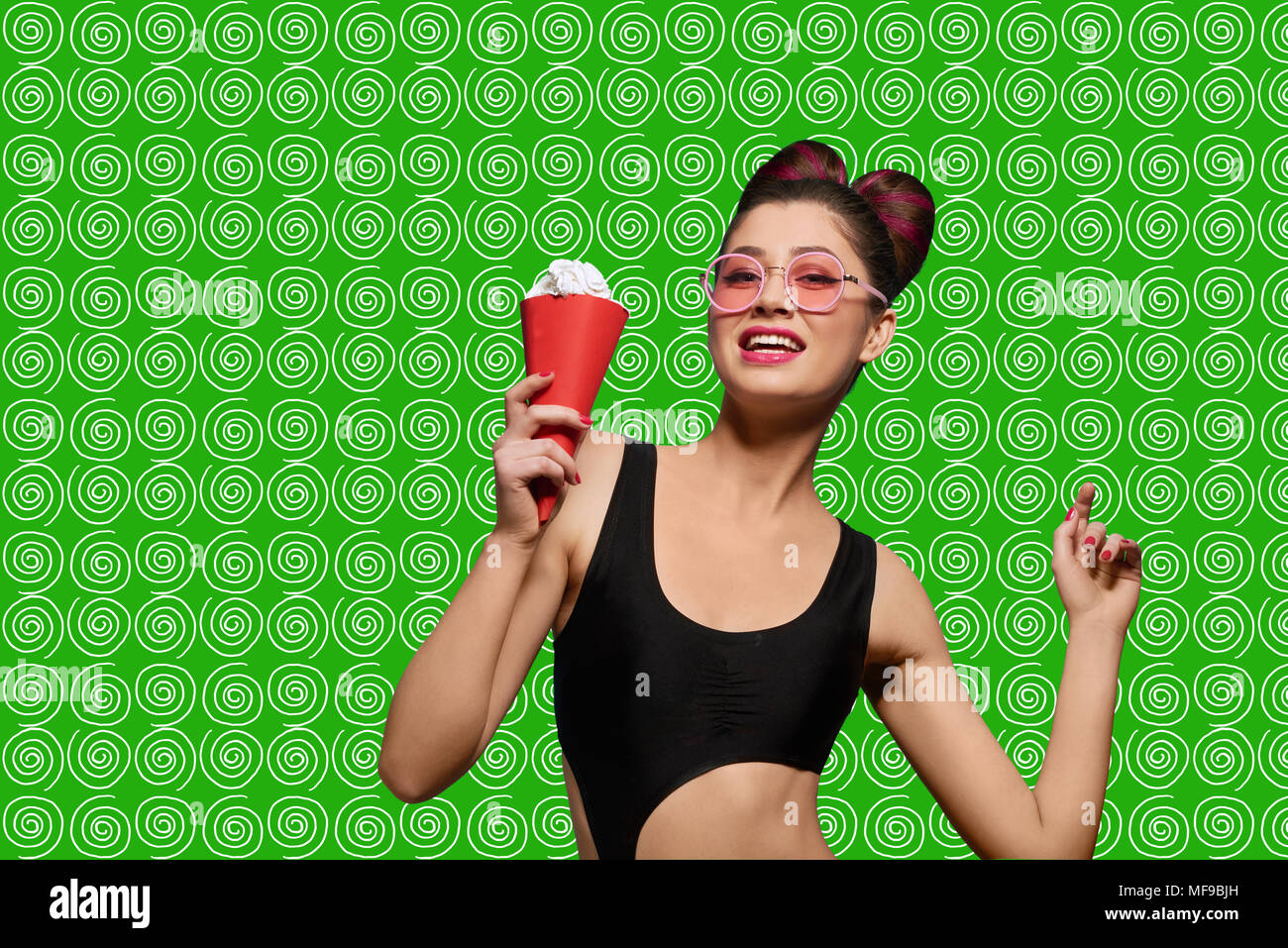 Fashion pop art model posing wearing pink sunglasses. Girl having black stylish swimwear, bright make up and fance hairstyle. Keeping ice cream in red horn. Saturated green background. - Stock Image