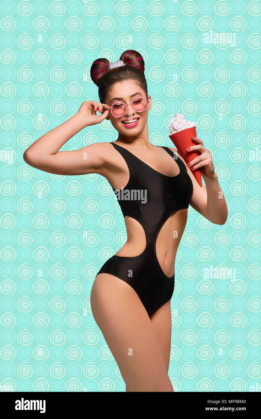 Posing stunning model with red ice cream horn, wearing fashionable black swimwear, pink sunglasses, fance hairstyle and bright make up. Standing on saturated blue and white background. - Stock Image