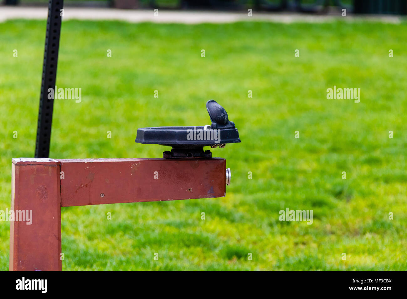 a lonely water fountain in a public park - Stock Image