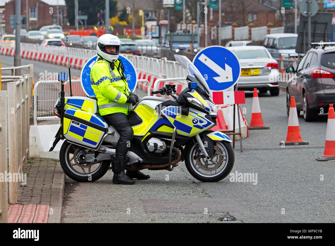 British motorcycle police officer on his BMW motorbike at the Grand National meeting in Liverpool 2018 Stock Photo