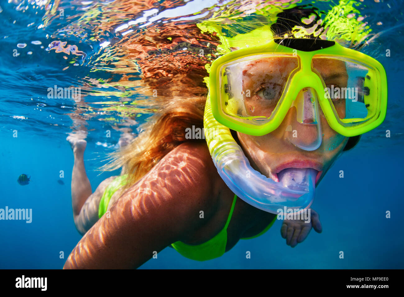Happy girl in snorkeling mask dive underwater with tropical fishes in coral reef sea pool. Travel lifestyle, water sports, outdoor adventure, swimming - Stock Image
