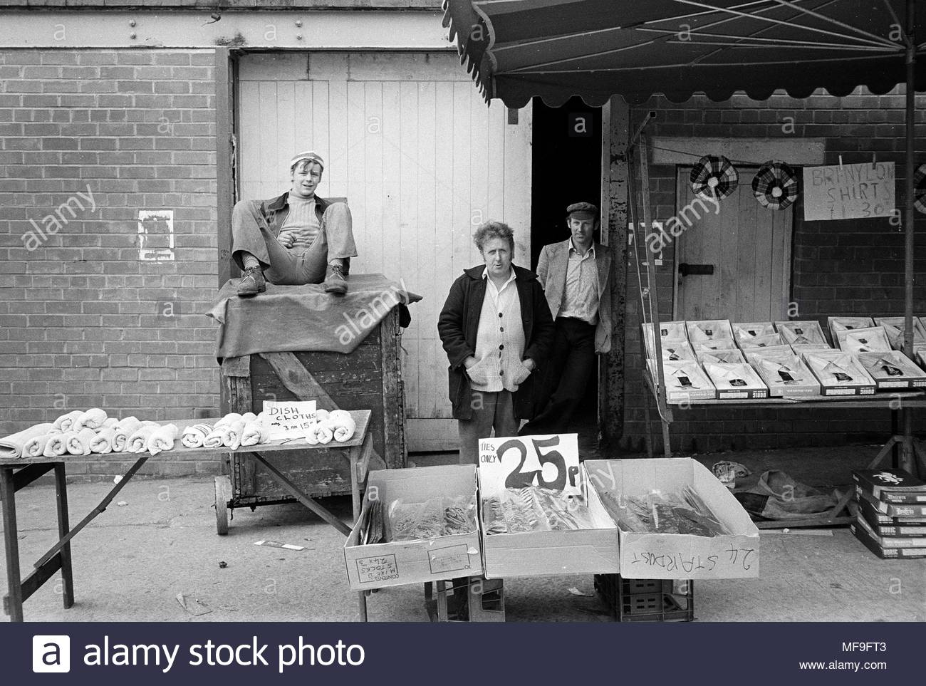 Male vendors on their stall on Tommyfield Market in Oldham Northwest England UK in the 1970s   photo DON TONGE Photographer - Stock Image