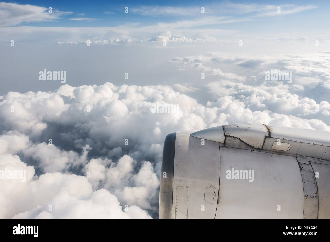 Slightly dirty airliner jet engine and cloudy sky, airplane in flight - Stock Image