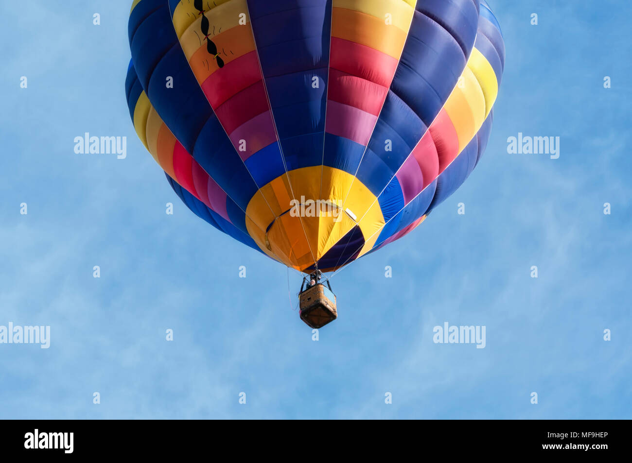 Close-up view from a low angle of a colorful hot-air balloon flying in the clear Italian sky above Udine in daylight. Concept for freedom & adventure Stock Photo