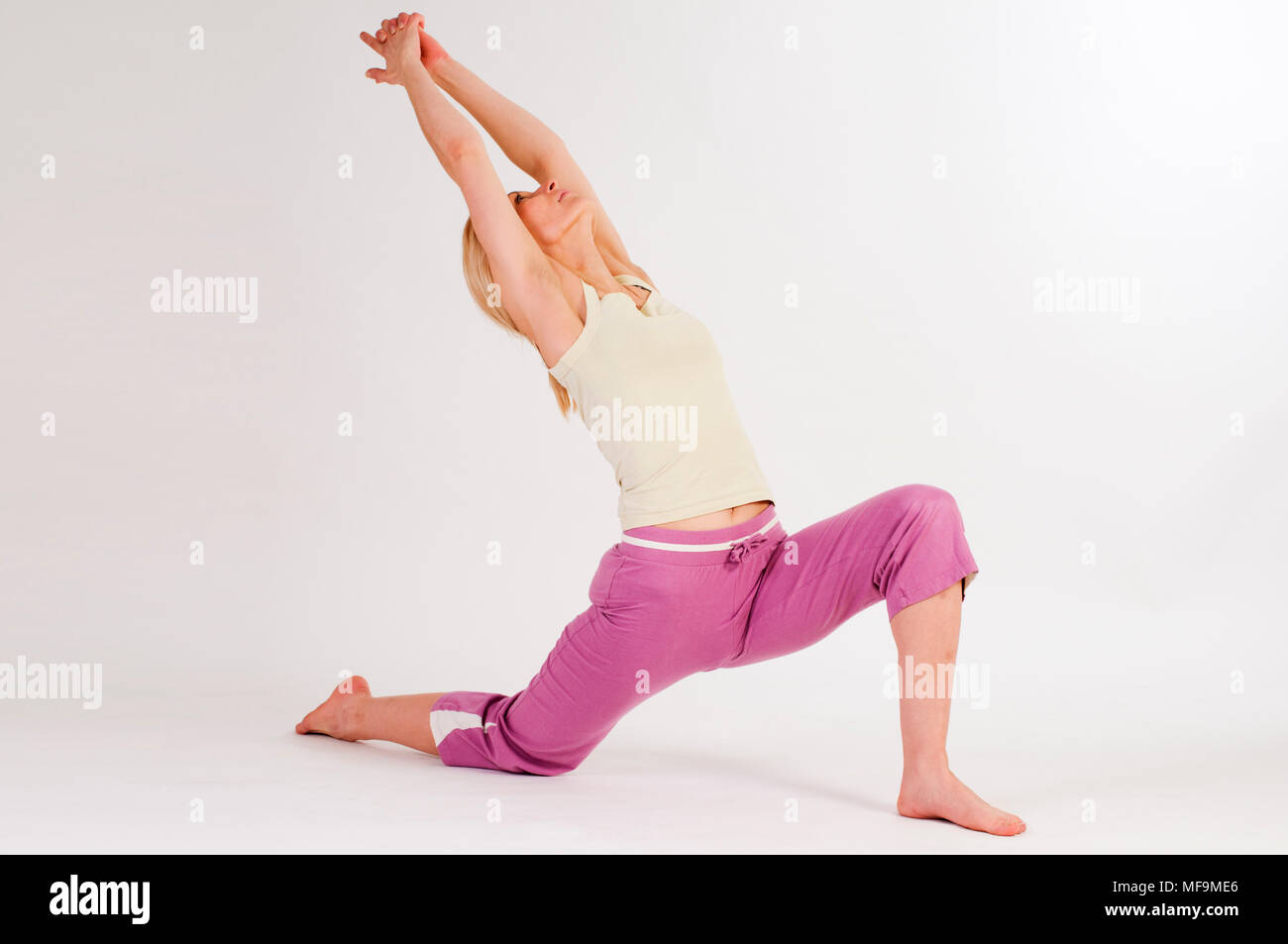Full-body view of a young woman on white background representing the yoga position The Moon. - Stock Image