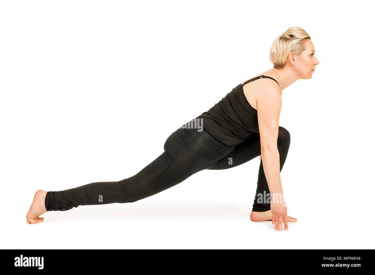 Seitliche Ganzkörper-Ansicht einer jungen Frau vor weißen Hintergrund die Yoga-Übung Ausfallschritt aus dem nach unten gerichteten Hund (adho mukha) - Stock Image