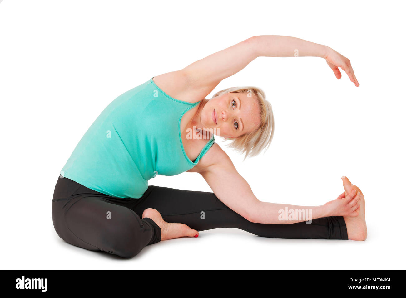 Full body view of a young blond woman doing yoga exercises in front of white background with gentle shadow. - Stock Image