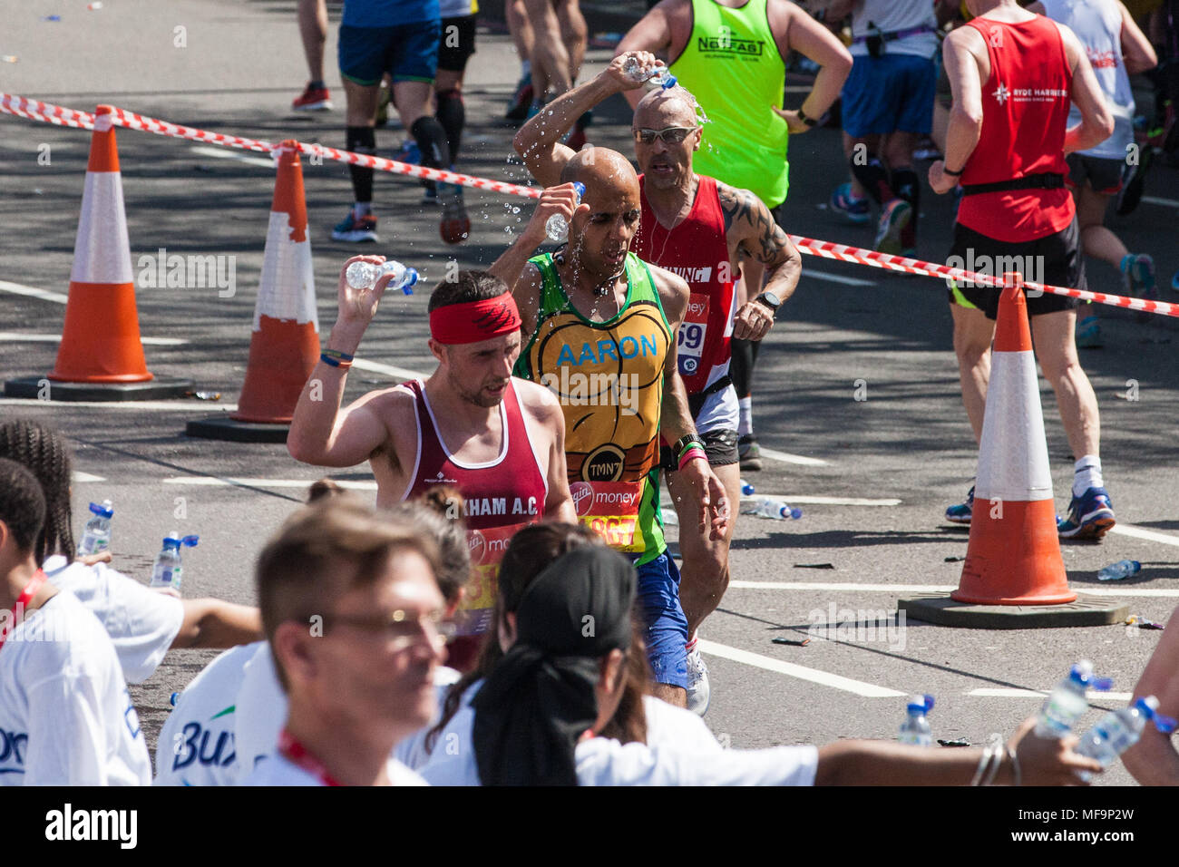London, UK. 22nd April, 2018. Runners take on water in record temperatures at the Virgin Money London Marathon. - Stock Image