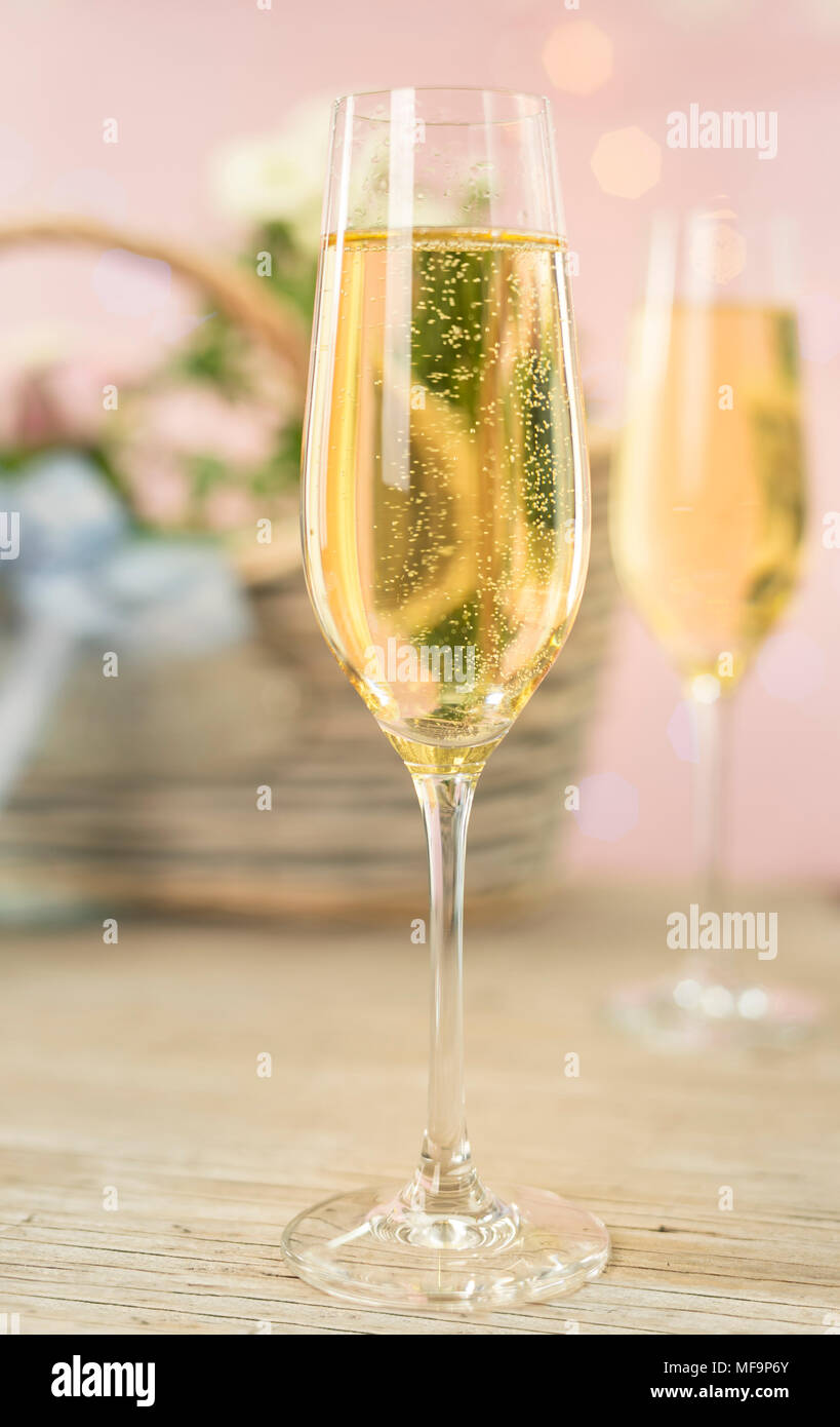 2 champagne glasses in front of spring flowers in pastel colored surroundings - Stock Image