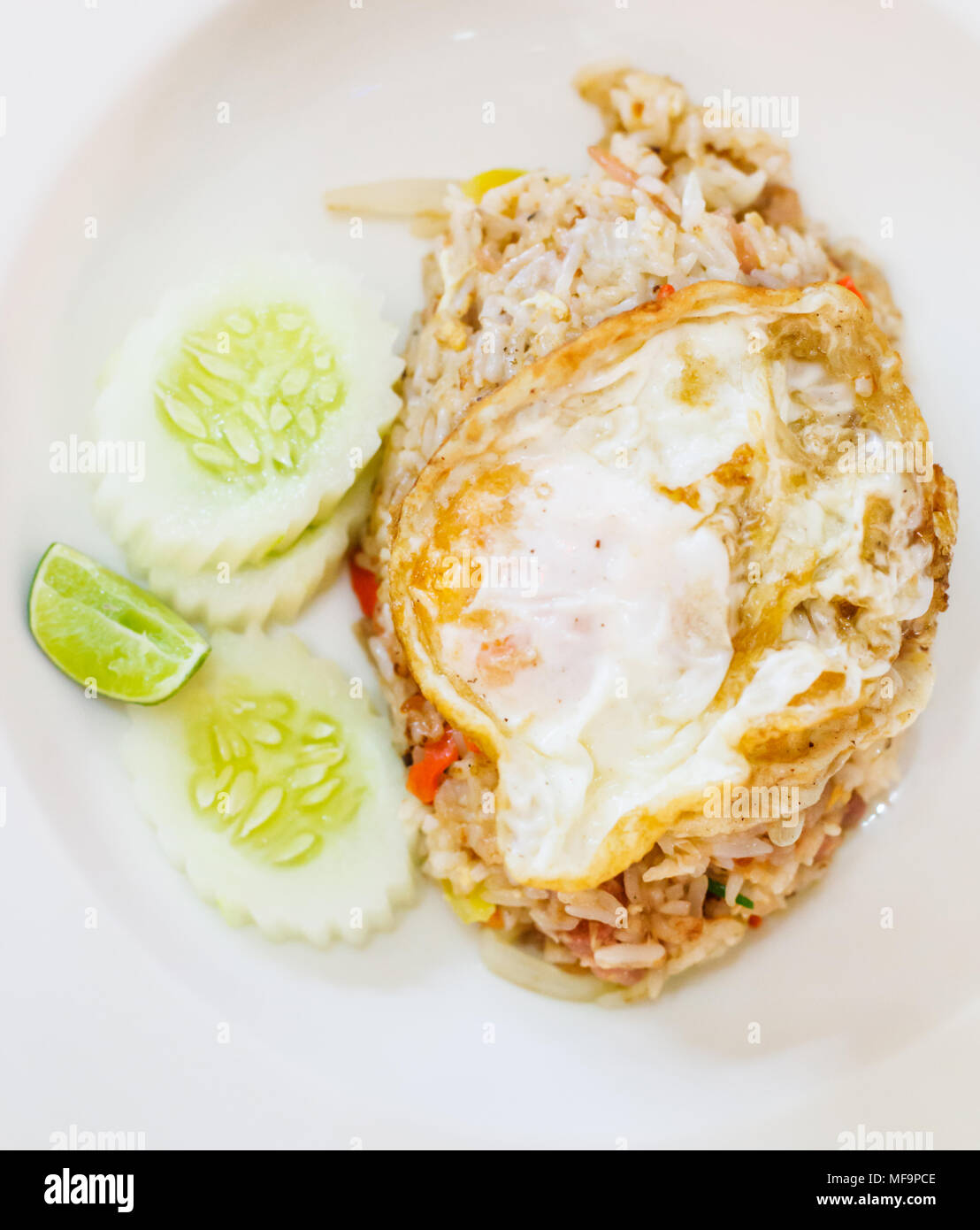 selective focus close up traditional Thai Asian cuisine food menu: delicious Thai fermented pork fried rice with fried egg on top garnished with lemon - Stock Image