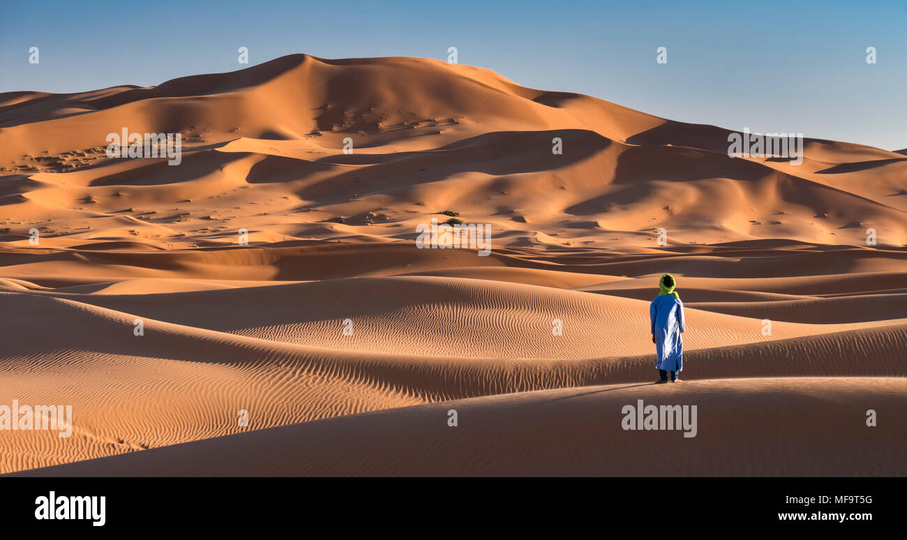 A Berber Man stands at the edge of the Sahara Desert, Erg Chebbi, near Merzouga, Morocco MODEL RELEASED - Stock Image