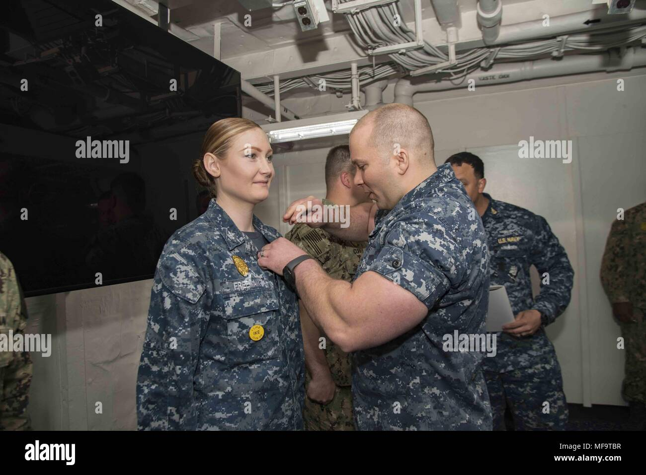 180423-N-LA456-0013 PORTSMOUTH, Va. (April 23, 2018) Master-At-Arms 1st Class Nancy Freeman receives her enlisted surface warfare specialist pin in the Five-Star classroom of the aircraft carrier USS Dwight D. Eisenhower (CVN 69) (Ike), April 23, 2018. Ike is undergoing a Planned Incremental Availability (PIA) at Norfolk Naval Shipyard during the maintenance phase of the Optimized Fleet Response Plan (OFRP). (U.S. Navy photo by Mass Communication Specialist Seaman Ashley M.C. Estrella). () - Stock Image