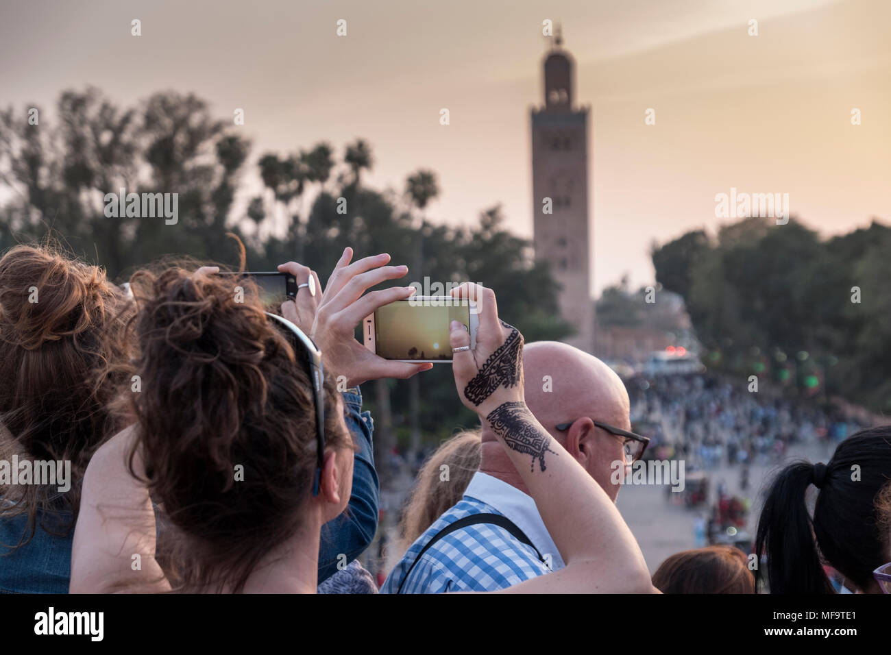 A Woman with Henna Tattoos on ther hands photographs the Koutoubia Mosque on her iphone at sunset, Marrakech, Morocco - Stock Image