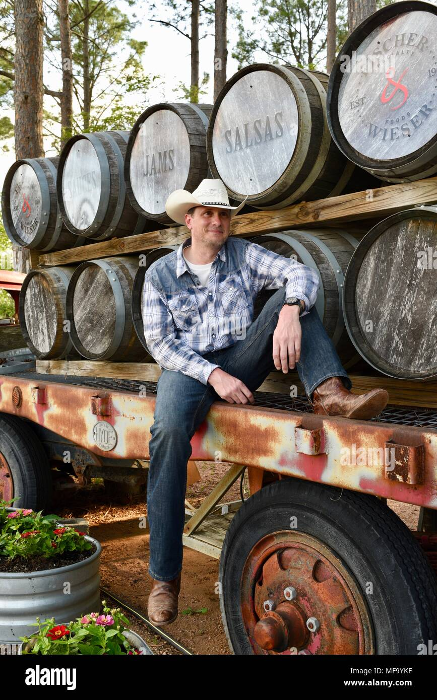Western Cowboy Sitting On Flatbed Trailer With Whisky Casks Or