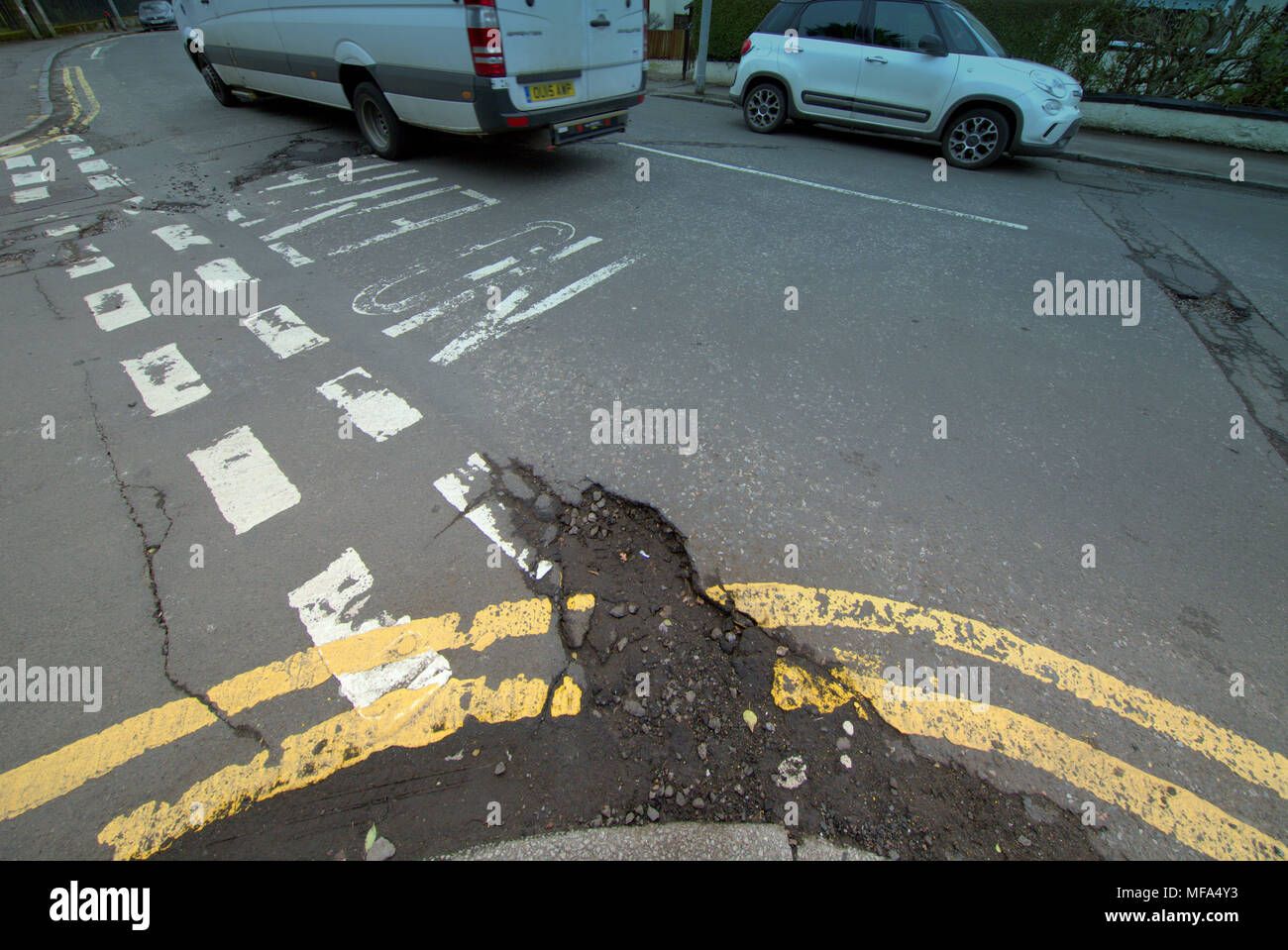 pot holes damaged road  car cars on street with  double yellow lines no entry markings Stock Photo