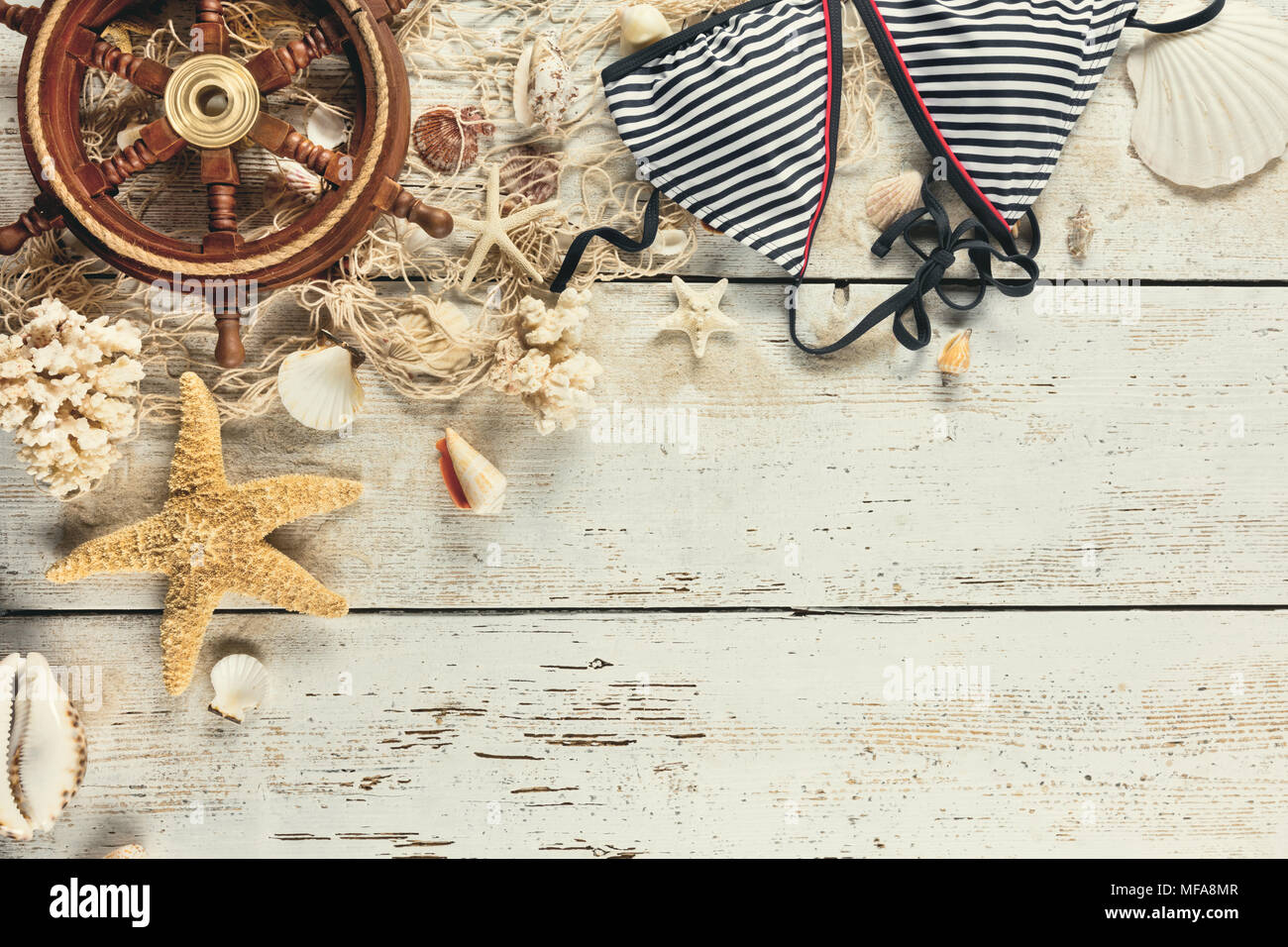 Seashells, swimming suit and wooden rudder with fishing net placed on old wooden planks in vintage colors. Copyspace for text. Very high resolution im - Stock Image