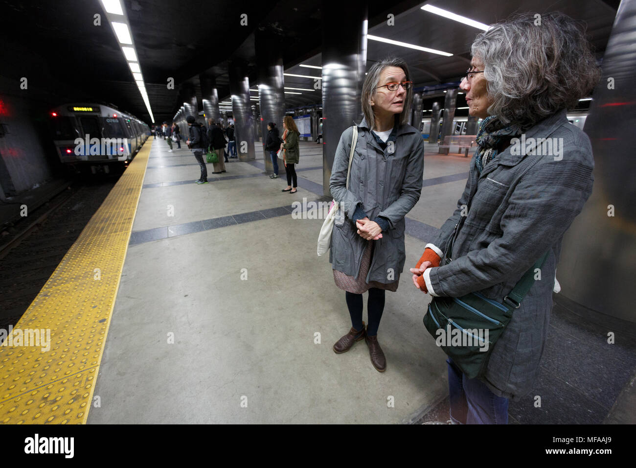 Women talking on a subway train platform. Maverick Station, Boston Massachusetts USA - Stock Image