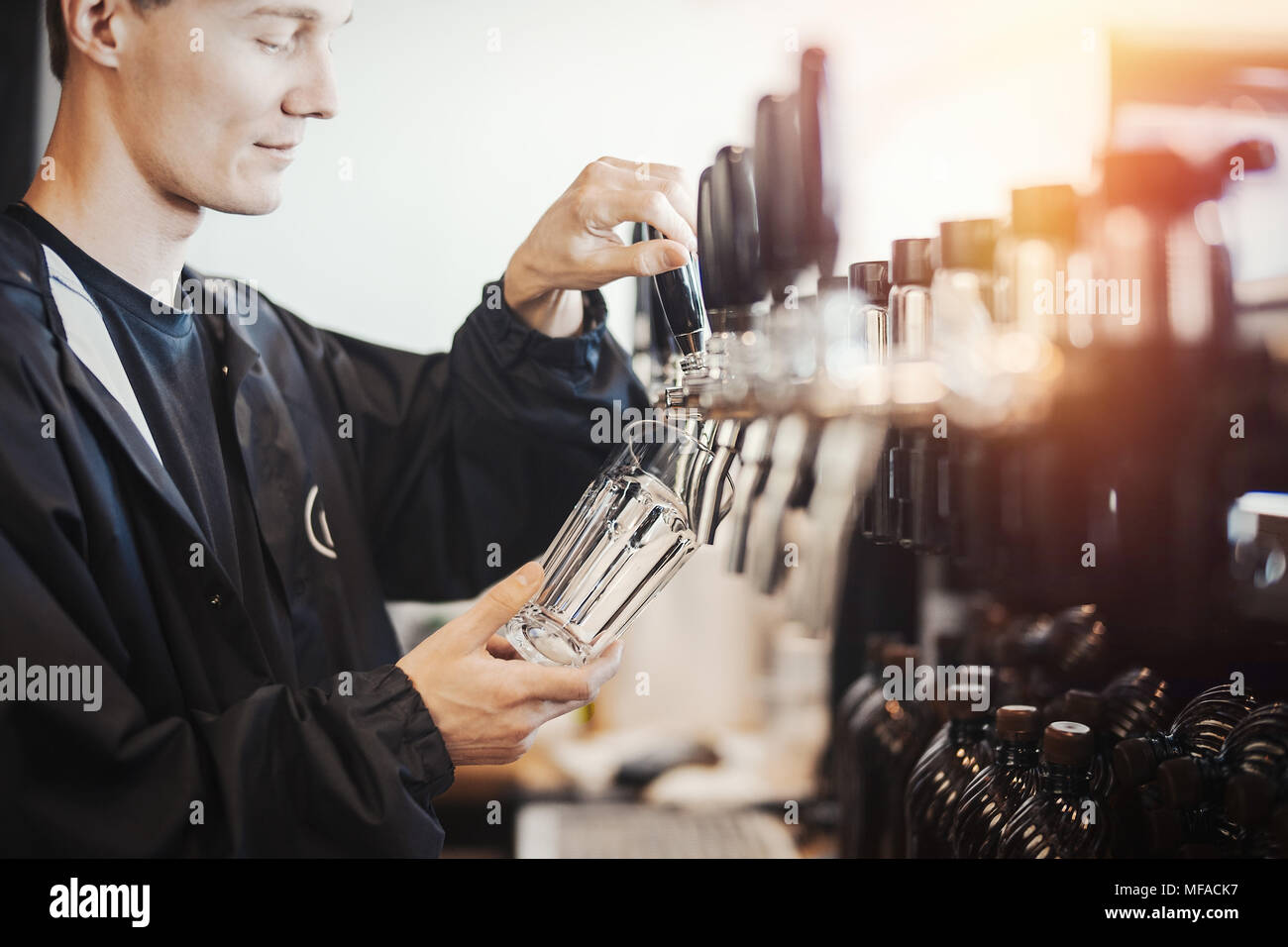Bartender man poors glass of beer. - Stock Image