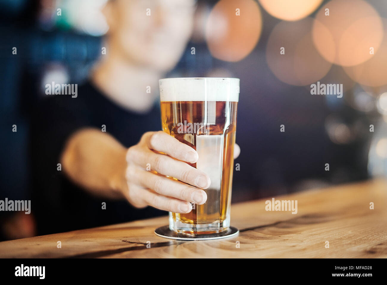 Bartender man stretches out a glass of beer. - Stock Image