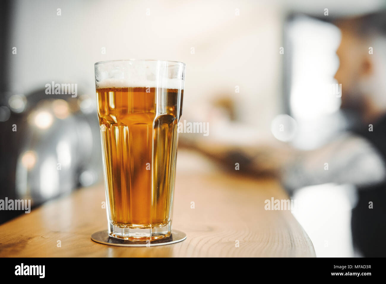 Beer glass stands on bar counter. - Stock Image