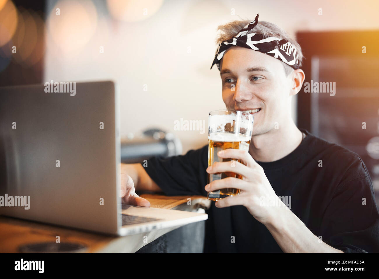 Young smiling man holding glass of beer and working on laptop. - Stock Image