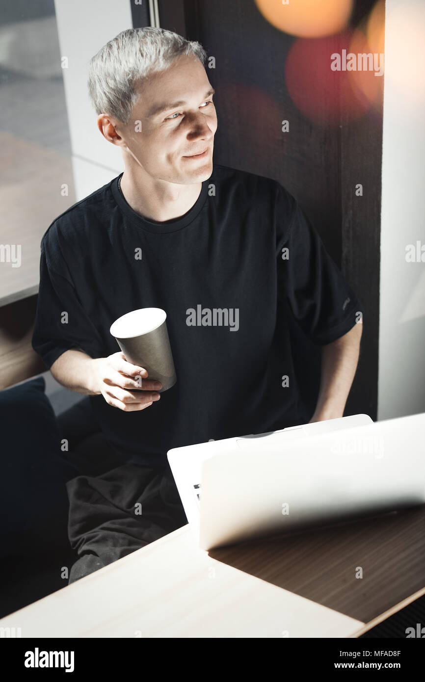 Young smiling man working on laptop and holding a cup of coffee. - Stock Image