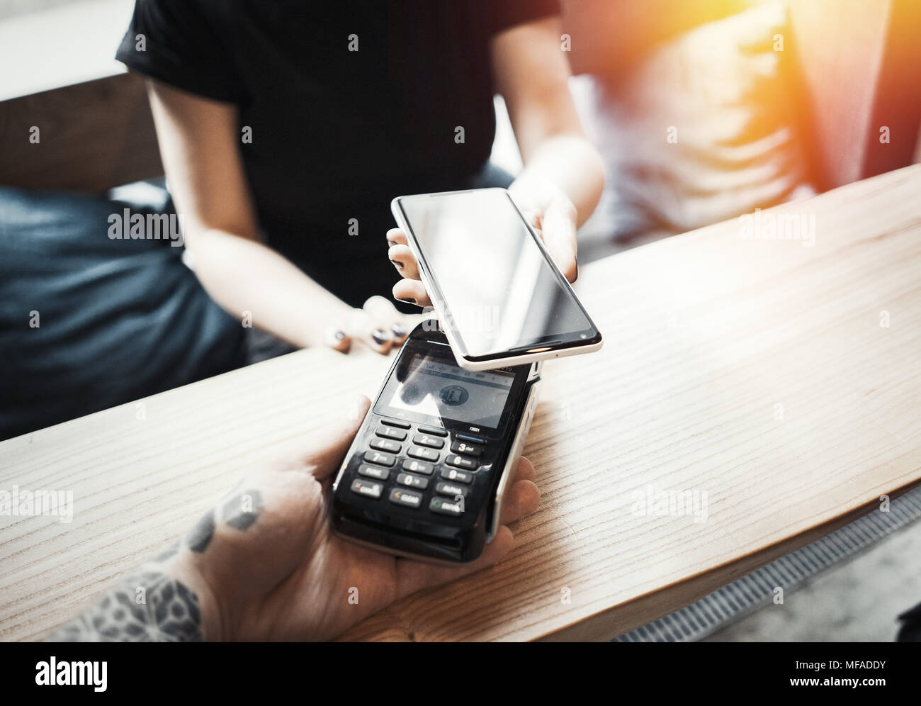 Young woman pays via payment terminal and mobile phone. - Stock Image