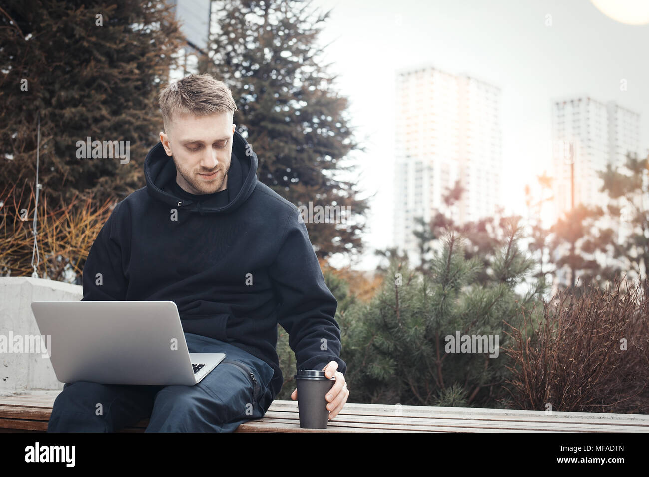 Young man holding laptop on knees. Black coffee cup is next to him. - Stock Image