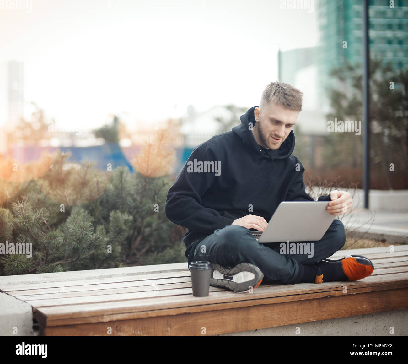 Smiling young man holding laptop on knees. Black coffee cup is next to him. - Stock Image