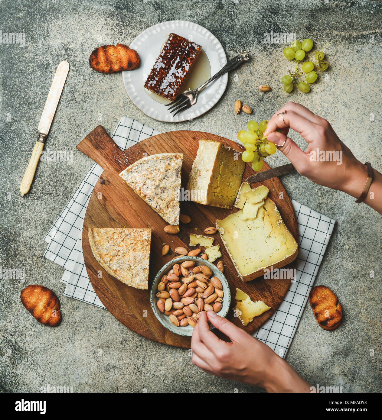 Cheese platter with female hands reaching to food - Stock Image