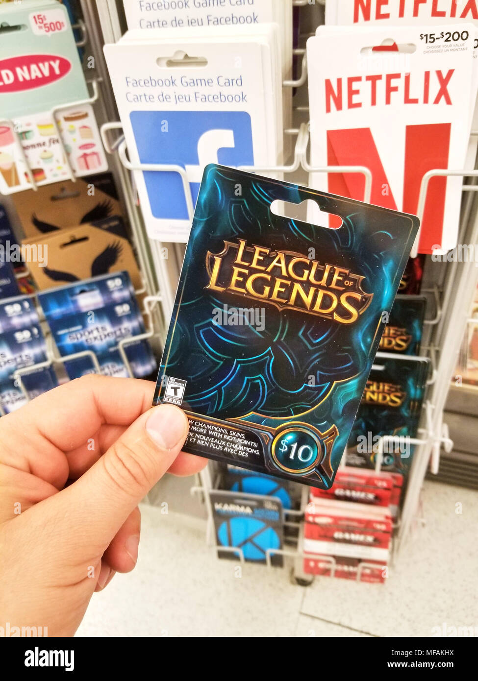 MONTREAL, CANADA - MARCH 31, 2018 : A hand holding a League of Legends gift card. League of Legends is a competitive online game that blends the speed - Stock Image