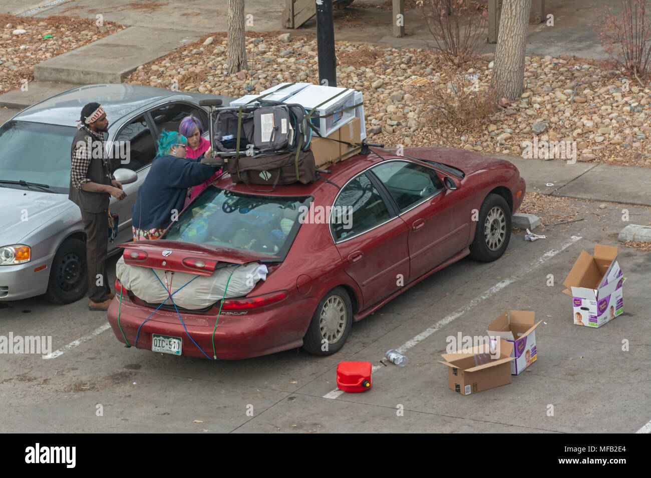 First of the month former renters of apartment building load all their belongings inside and on roof of car to move out, Aurora Colorado US. - Stock Image