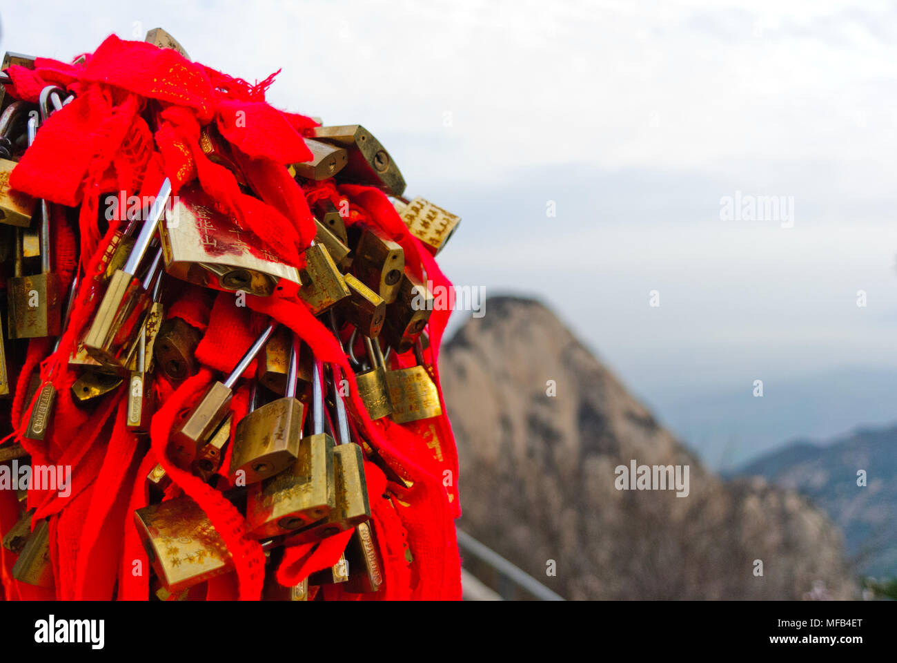 Locks with red bows on mountain Huashan in China - Stock Image