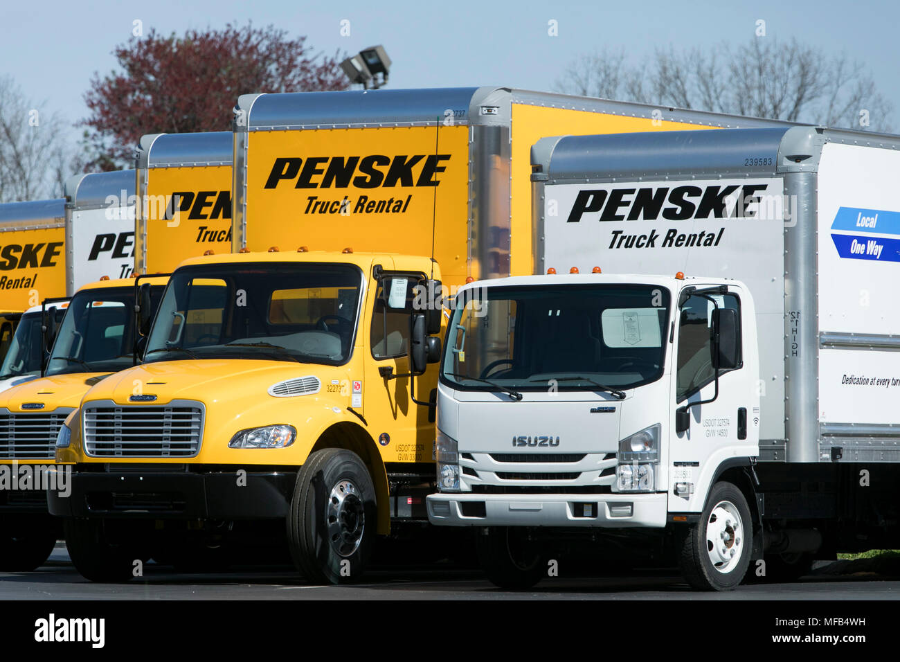 A Logo Sign And Rental Trucks Outside Of A Facility Occupied By