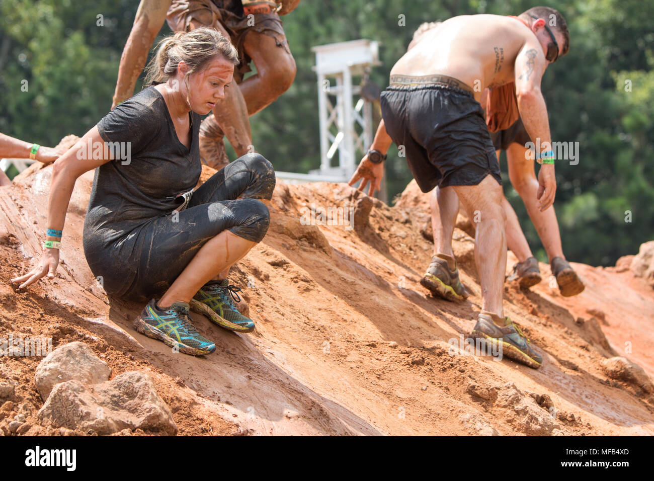 Competitors carefully make their way down a large slippery dirt mound at the Rugged Maniac Obstacle Course race on August 22, 2015 in Conyers, GA. - Stock Image