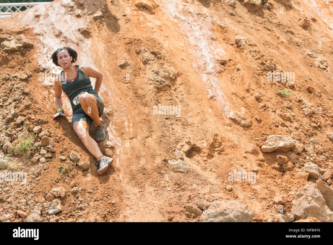 A young woman struggles to make her way down a slippery dirt hill at the Rugged Maniac Obstacle Course on August 22, 2015 in Conyers, GA. - Stock Image