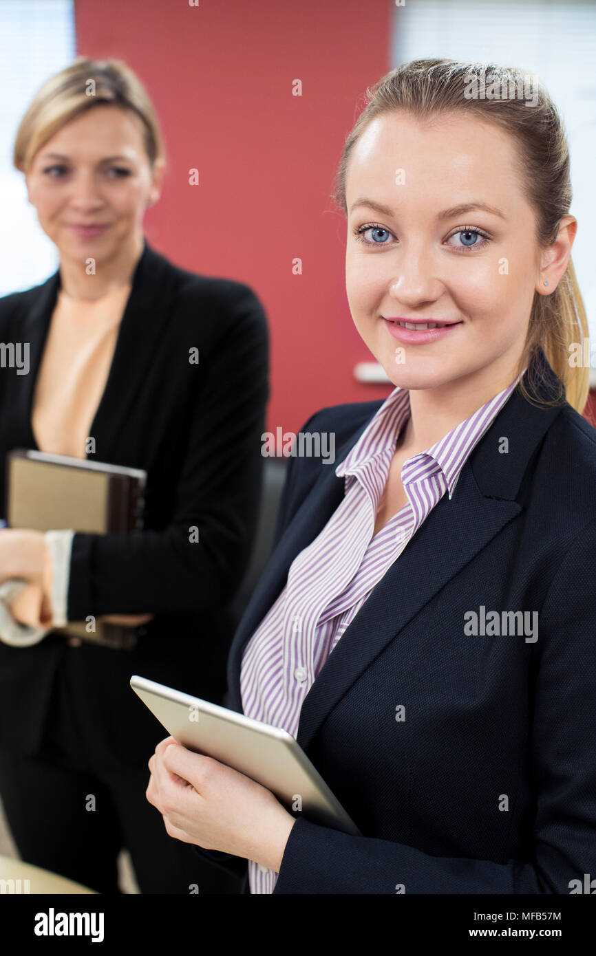 Portrait Of Young Businesswoman With Felame Mentor In Office - Stock Image