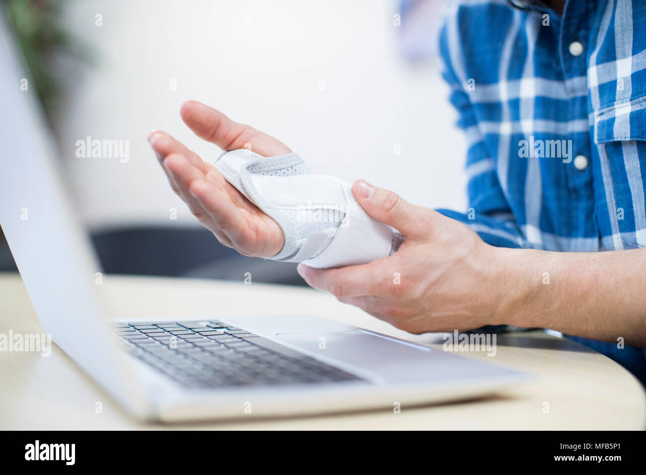 Close Up Of Businessman Using Laptop Suffering From Repetitive Strain Injury (RSI) - Stock Image