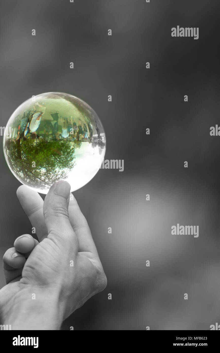 black and white image of hand holding green glass crystal ball between thumb and forefinger - Stock Image