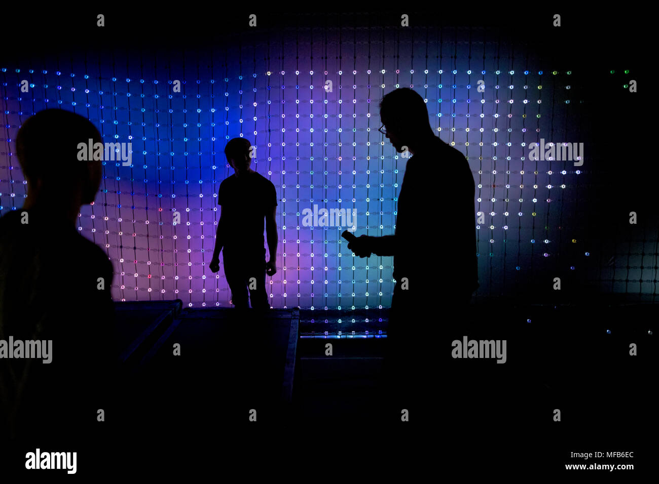 People in the background of the LED panel - Stock Image