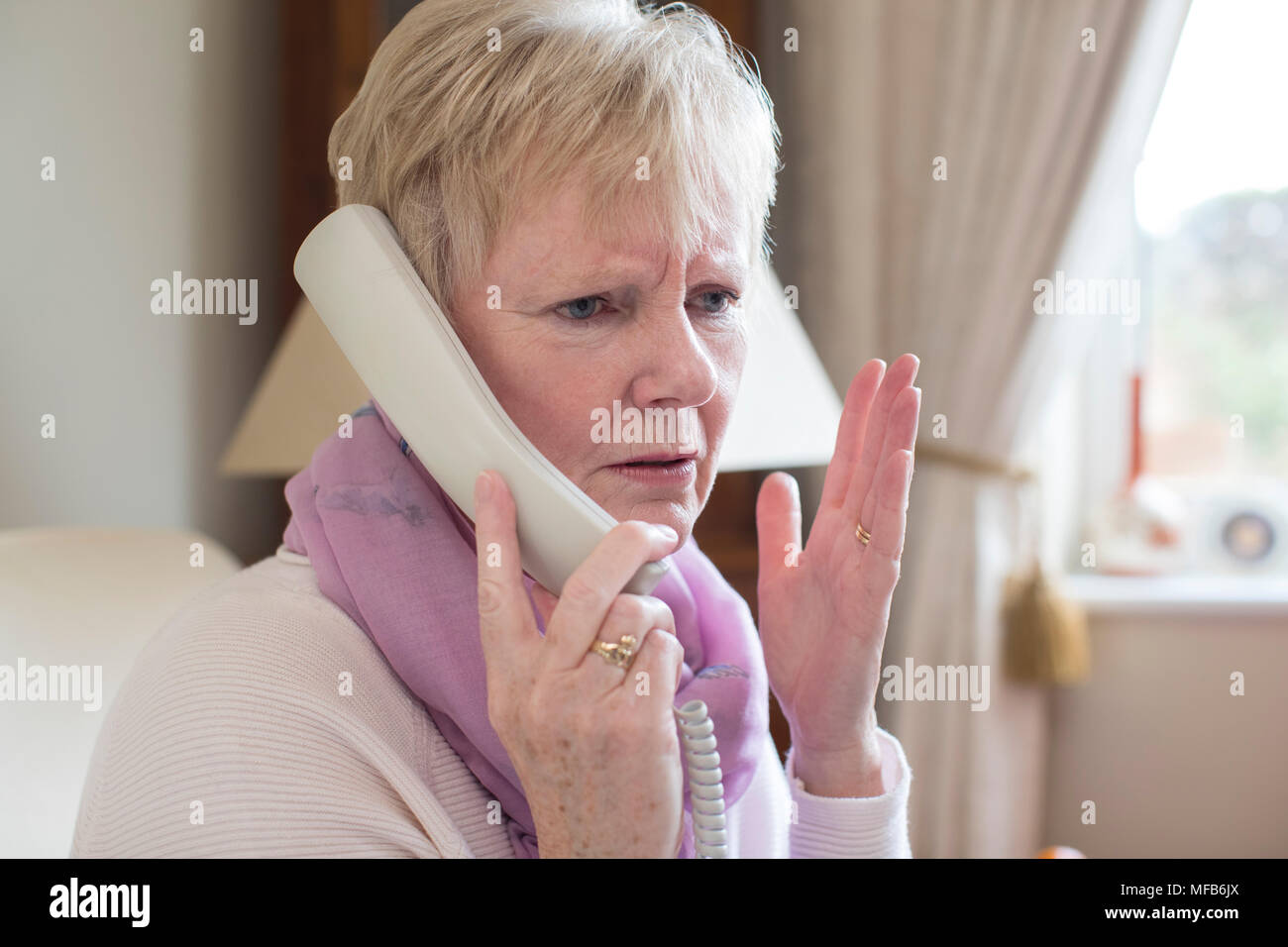 Senior Woman Receiving Unwanted Telephone Call At Home - Stock Image