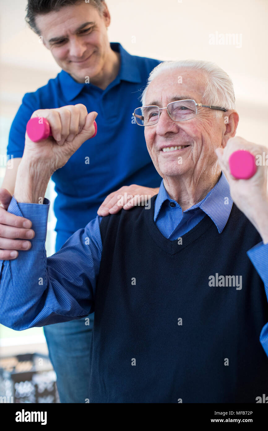 Physiotherapist Helping Senior Man To Lift Hand Weights - Stock Image