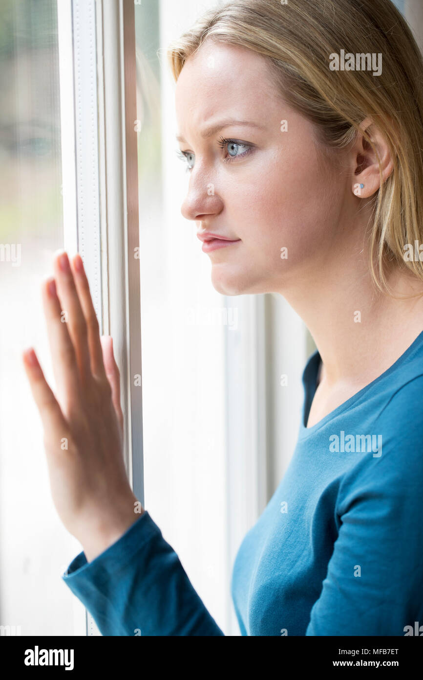 Sad Young Woman Suffering From Depression Looking Out Of Window - Stock Image